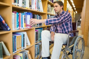 Man in wheelchair selecting book from bookshelf in the library